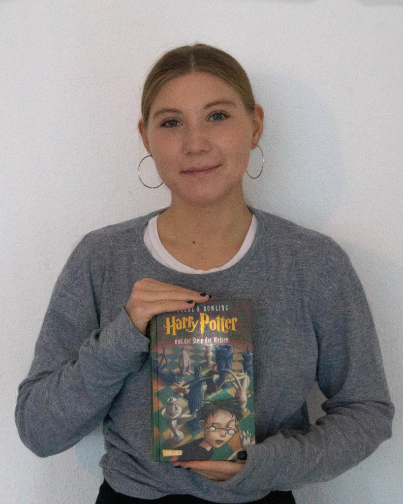"""Lara Glockner mit einem Buch """"Harry Potter und der Stein der Weisen"""""""