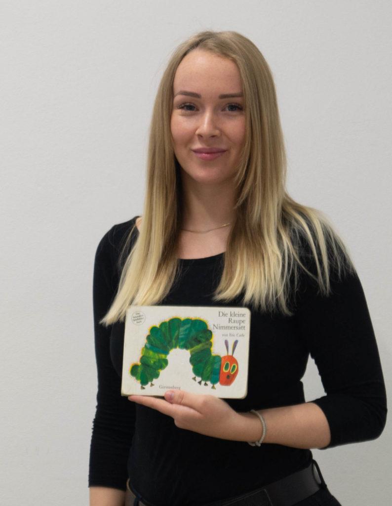 """Annika Manheller mit einem Buch """"Die kleine Raupe Nimmersatt"""""""