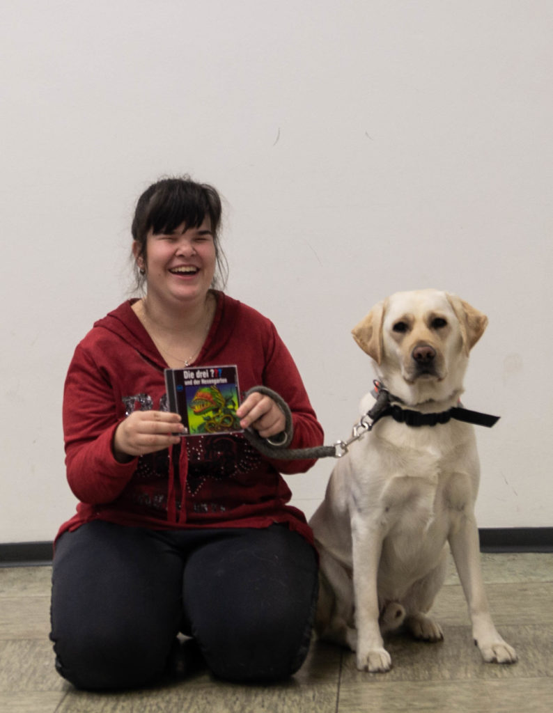 Carina Tillmann mit Blindenführhund Pitou und einer drei ??? CD