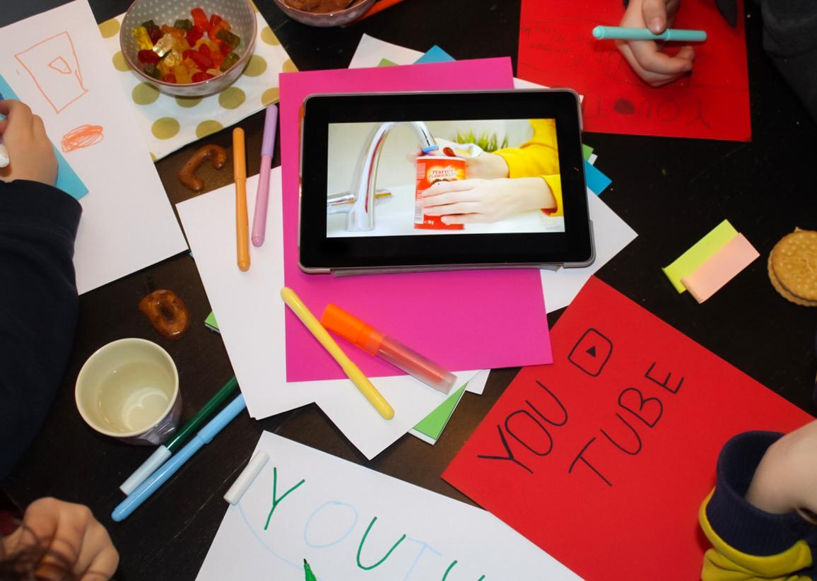 einn Tisch voll mit selbstbeschrifteten Plakaten und einem Tablet in der Mitte, das Werbung zeigt