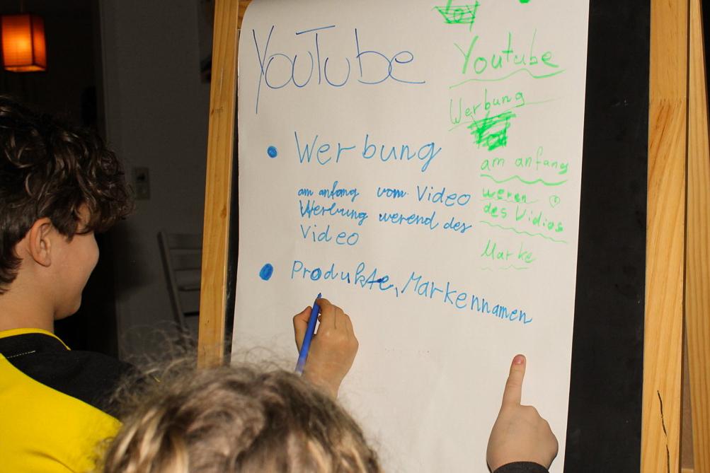 Kinder vor einer Tafel, die auf ein Plakat schreiben